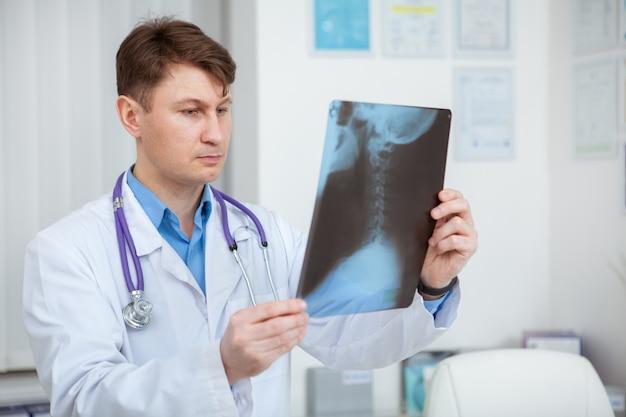 Médico varón maduro examinar exploración de rayos x, trabajando en su oficina