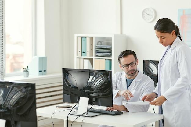 Médico varón maduro sentado en su lugar de trabajo frente a la computadora y discutir documentos con la enfermera en la oficina