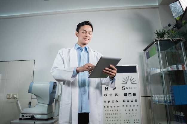 Un médico varón mantiene una lista de verificación de la vista que constituye la base de los exámenes en la clínica oftalmológica.