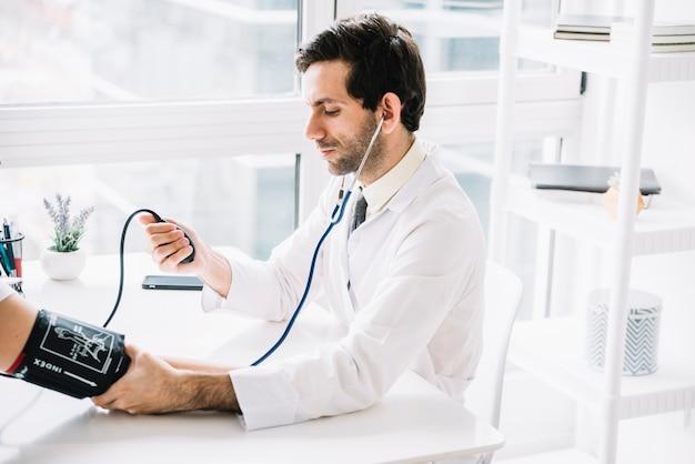 Médico varón medir la presión arterial del paciente en la clínica