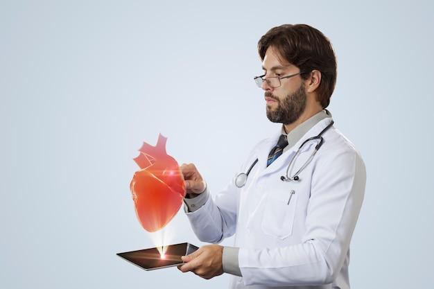 Médico varón mirando un corazón virtual que sale de una tableta en una pared gris
