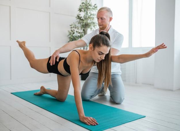 Médico varón y mujer durante una sesión de fisioterapia