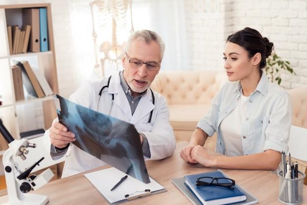 Médico varón y paciente femenino en oficina