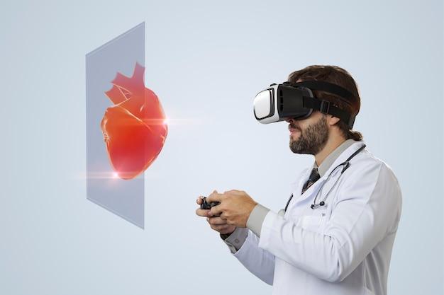 Médico varón en una pared gris con gafas de realidad virtual, mirando un corazón virtual