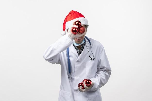 Médico varón sosteniendo juguetes de plástico covid virus salud emoción