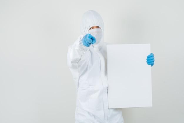 Médico varón sosteniendo un lienzo en blanco, apuntando a la cámara en traje protector
