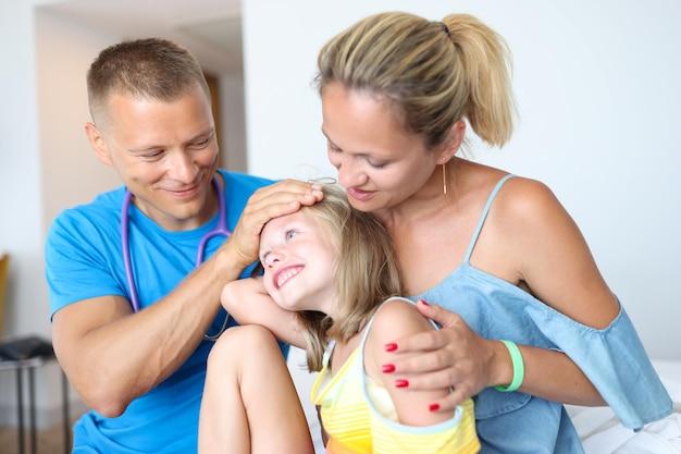 Médico varón tocando la frente de la niña enferma en la clínica concepto de medicina familiar