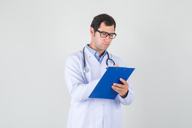 Médico varón tomando notas en el portapapeles en bata blanca, gafas y mirando ocupado. vista frontal.