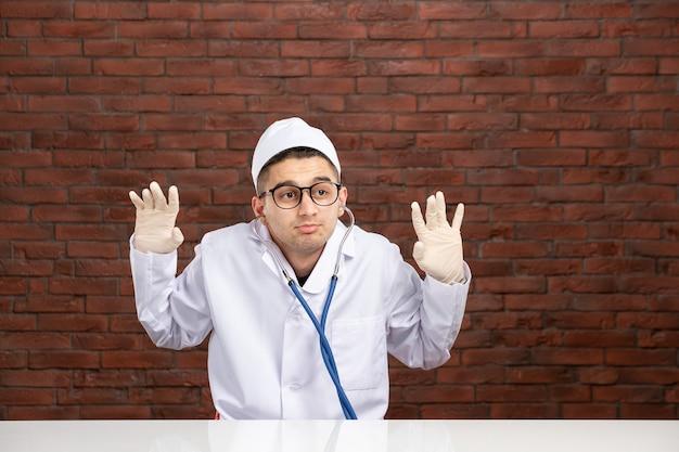 Médico varón de vista frontal en traje médico blanco con estetoscopio
