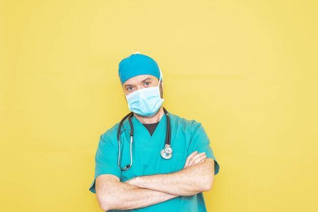 Médico vestido de cirujano en verde con estetoscopio y máscara sobre un fondo amarillo con expresión preocupada.