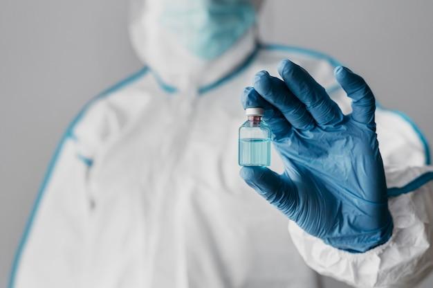 Médico de vista frontal sosteniendo una botella de vacuna