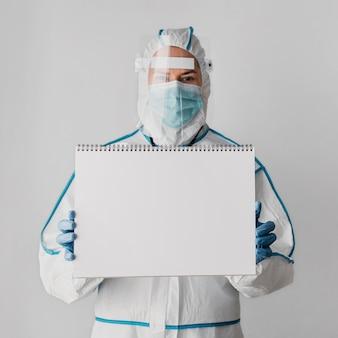 Médico de vista frontal sosteniendo un cuaderno en blanco