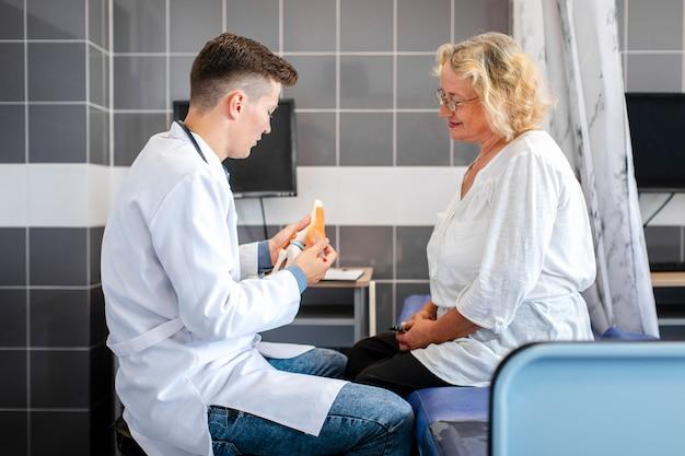 Médico de vista lateral que muestra las articulaciones óseas a un paciente