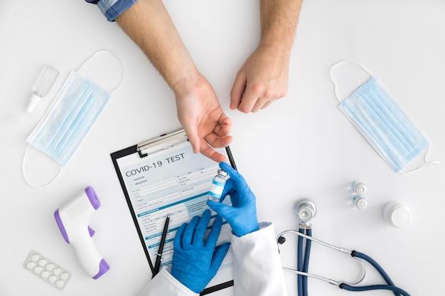 Médico de vista superior dando vacuna covid