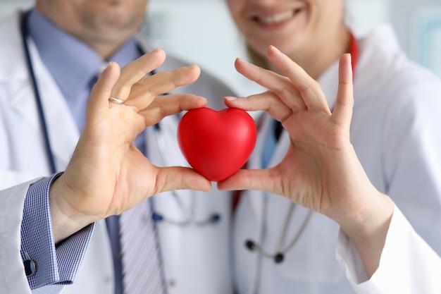 Los médicos en batas blancas sostienen el corazón, se centran en el corazón.