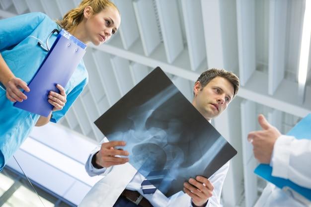 Médicos y cirujano hablando de rayos x