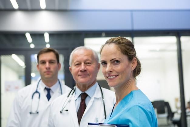 Médicos y cirujano sonrientes parados juntos en el hospital