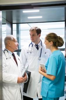 Médicos y cirujanos interactuando entre sí en ascensor.