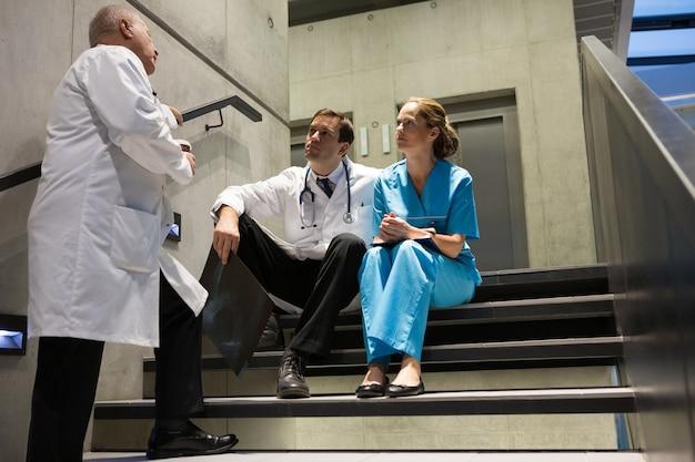 Médicos y cirujanos interactuando entre sí en la escalera.