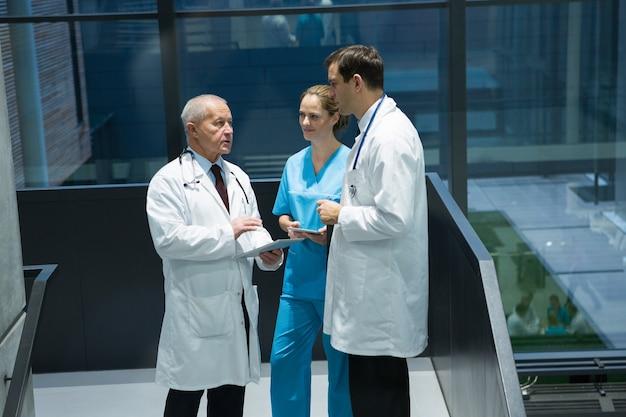 Médicos y cirujanos interactuando entre sí en el pasillo.