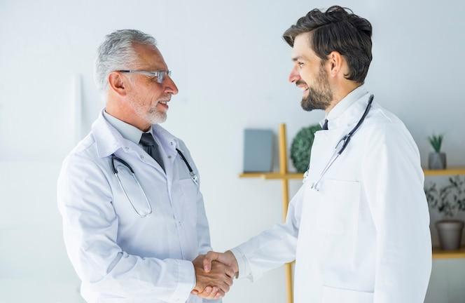 Médicos dándose la mano y mirándose