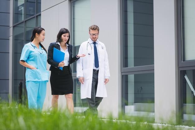 Médicos y enfermeras interactuando mientras caminan.