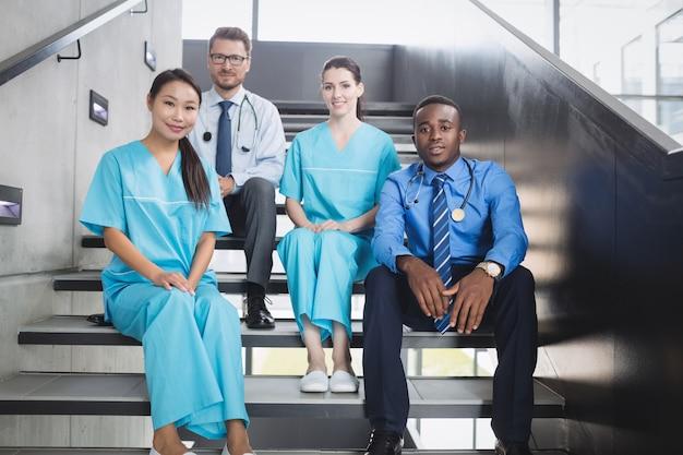 Médicos y enfermeras sentados en la escalera