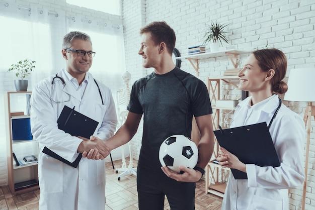 Los médicos están hablando con el jugador de fútbol.