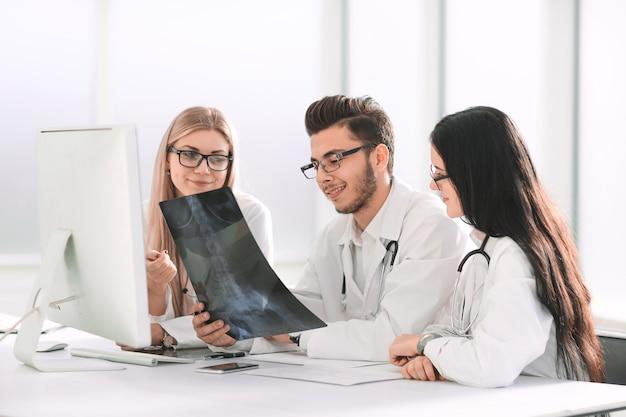 Los médicos expertos discuten rayos x, sentados en la mesa