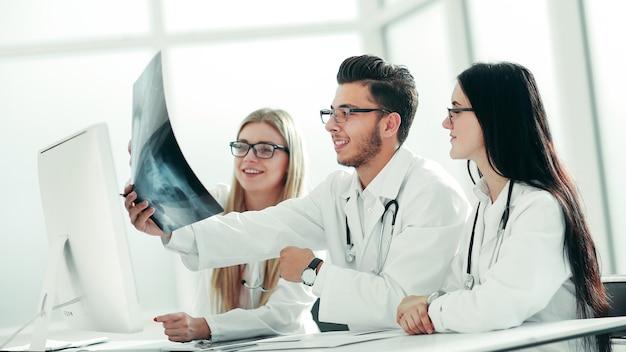 Los médicos expertos discuten rayos x sentados en la mesa