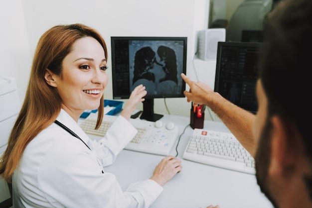 Médicos felices examinando tomografía computarizada de los pulmones.