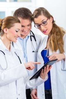 Médicos, hombres y mujeres, discutiendo los informes de las pruebas que se muestran en su tableta.