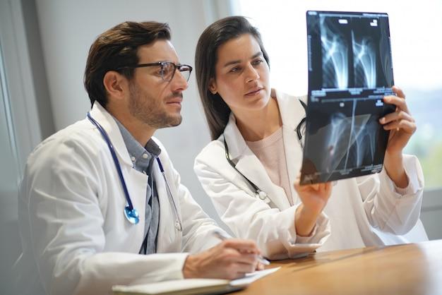 Médicos hombres y mujeres revisando los resultados del paciente.