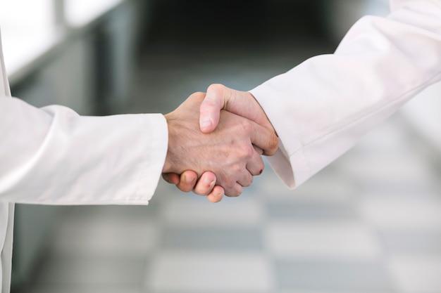 Médicos irreconocibles dándose la mano