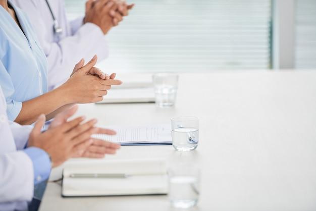 Médicos irreconocibles sentados en la conferencia, con cuadernos y agua en vasos, y aplaudiendo