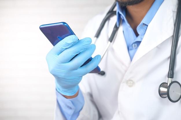 Los médicos de la mano en guantes protectores con un teléfono inteligente