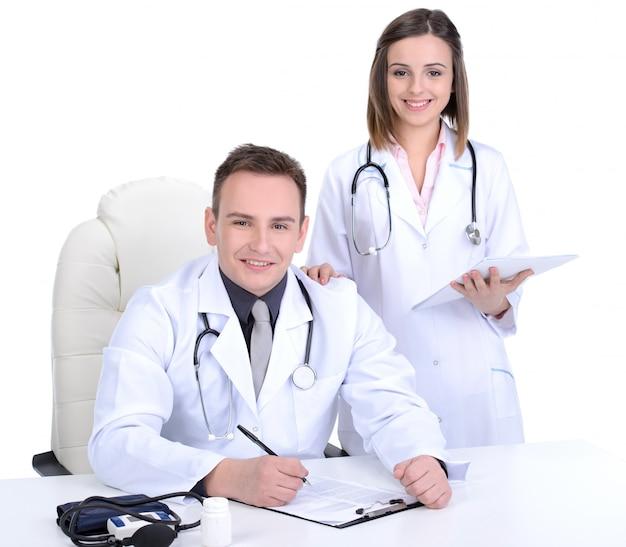 Médicos masculinos y femeninos posan juntos.