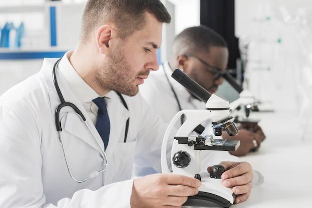 Médicos con microscopios en el laboratorio