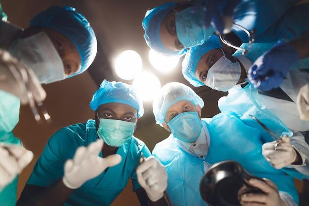 Los médicos miran al paciente, que yace en la mesa de operaciones.