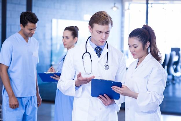 Médicos mirando informe médico y teniendo una discusión