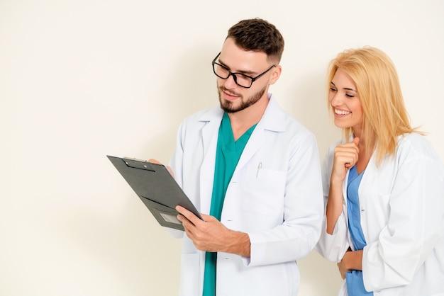 Médicos mirando y discutiendo en documentos de papel.