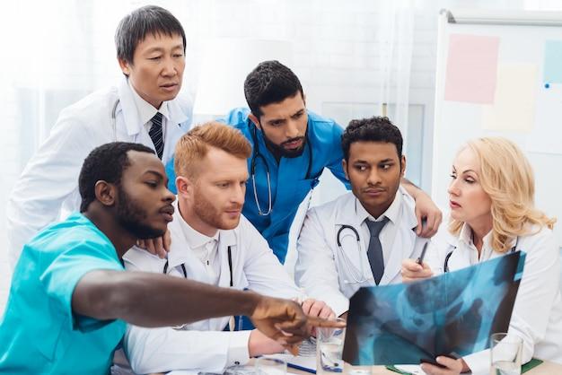 Médicos multinacionales examinan la radiografía del paciente.