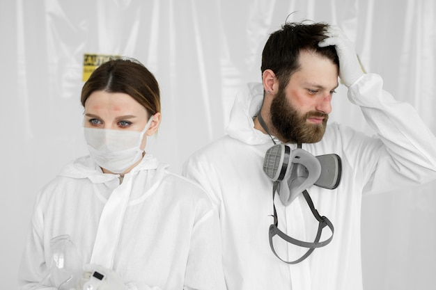 Médicos o enfermeras agotados tomando uniforme de máscara protectora.
