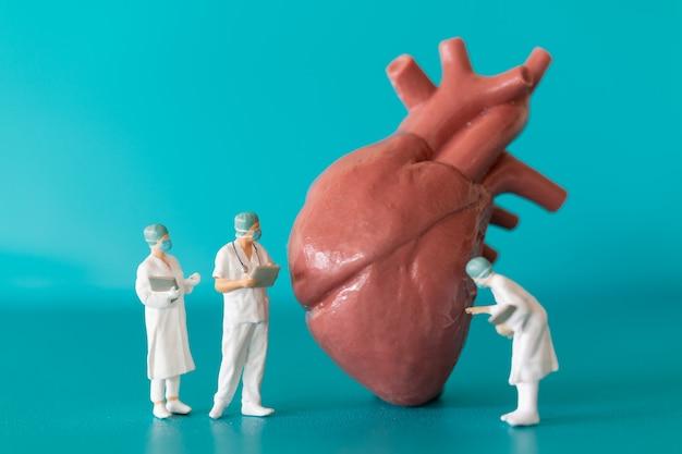 Médicos de personas en miniatura observando y discutiendo sobre el modelo de corazón humano sobre fondo azul.