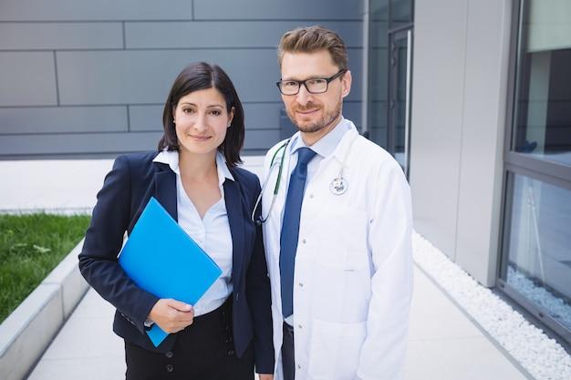 Médicos de pie juntos en las instalaciones del hospital.