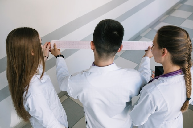 Médicos de pie y viendo cardiograma