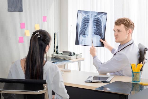 Médicos profesionales hombre caucásico con rayos x y conversación con el paciente.