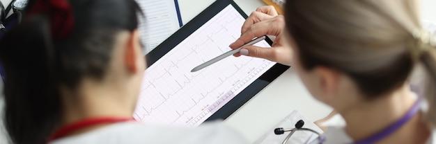 Médicos que estudian electrocardiograma en primer plano de tableta digital