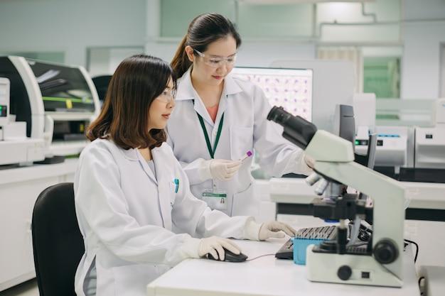 Médicos que trabajan para analizar muestras de sangre en laboratorio para investigación científica