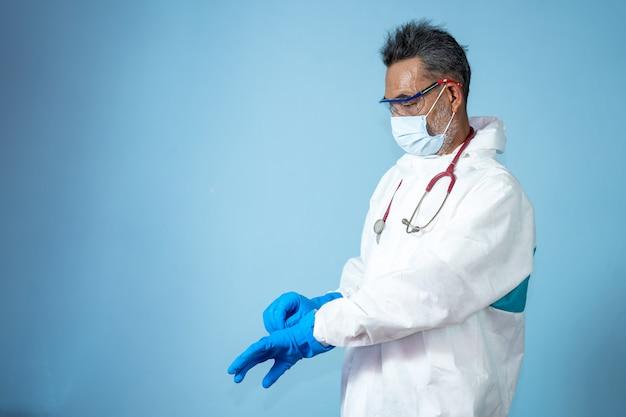 Los médicos con ropa protectora de ppe para materiales peligrosos usan guantes médicos de goma para proteger la enfermedad del coronavirus 2019 (covid-19)